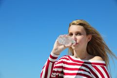 Thirsty woman drinking water. Against blue sky royalty free stock photography