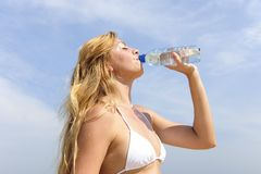 Thirsty woman drinking water outdoors Stock Photo