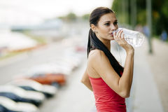 Thirsty woman drinking water to recuperate Stock Image