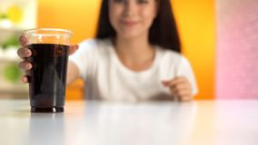 Thirsty woman taking soft drink with ice, plastic glass standing on table, sugar. Stock photo royalty free stock photo