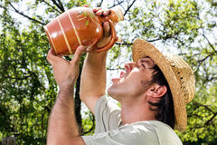 Thirsty young man with straw hat drinking water from a ceramic j Royalty Free Stock Photography