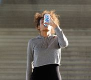 Thirsty young woman drinking from water bottle Royalty Free Stock Images