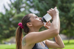 Thirsty young woman drinking water while resting Royalty Free Stock Photo
