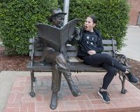 Thirteen year-old girl posing humorously with bronze of Will Rogers on a bench, Claremore, Oklahoma. Pictured is a thirteen year old Amerasian girl humorously Stock Photo