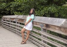 Thirteen yearold Amerasian girl posing on a wooden bridge in Washington Park Arboretum, Seattle, Washington. Pictured is a thirteen year-old Amerasian girl stock image
