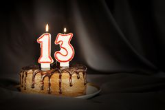 Thirteen years anniversary. Birthday chocolate cake with white burning candles in the form of number Thirteen. Dark background with black cloth stock photography