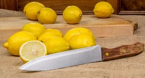 Thirteen yellow lemons on a wooden board and canvas  and a knife in the foreground Stock Images