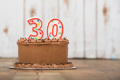 Thirtieth chocolate frosted birthday cake Stock Photos