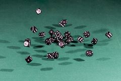 Thirty Black Dices Falling On A Green Table Stock Photos