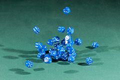 Thirty blue dices falling on a green table stock photos