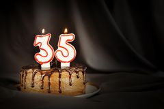 Thirty five years anniversary. Birthday chocolate cake with white burning candles in the form of number Thirty five. Dark background with black cloth royalty free stock photos