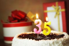Thirty five years birthday. Cake with burning candles and gifts Stock Images