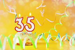 Thirty five years birthday. Cupcake with burning candles in the form of number 35 royalty free stock image