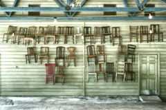 Thirty Hanging Chairs and a Door. Thirty chairs hanging on a wooden lap sided wall next to a door inside a Texas party hall photographed on the back roads of stock photography