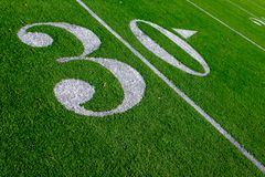 Thirty more yards to pay dirt. Yard line and numbers on a university`s artificial turf football practice field Stock Photo
