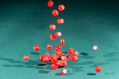 Thirty red dices falling on a green table stock images
