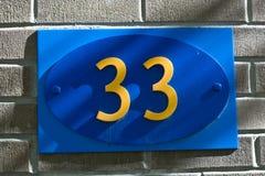 Thirty Three. A sign displaying thirty three, on a grey brick wall in Toronto Stock Photos
