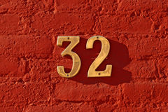 Thirty Two. Painted red brick wall with shiny brass numbers Royalty Free Stock Photo