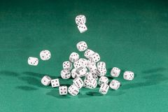 Thirty white dices falling on a green table stock photos