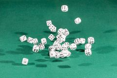 Thirty white dices falling on a green table royalty free stock photo