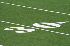 Thirty Yard Line Football. White thirty yard line numbers on a football field with artificial turf Stock Photos