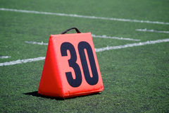Thirty Yard Line Marker. Orange yard marker designates the thirty yard line on a football field Stock Photos