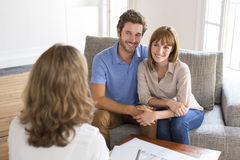 Thirty year old couple meeting financial adviser for investment. Young happy couple meeting a consultant before investing in real estate Stock Images