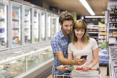 Thirty-year-old couple using mobile phone in supermarket stock photos