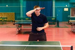 Thirty-year-old man in black sports uniform playing table tennis in the gym. Roll right in table tennis stock photography