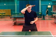 Thirty-year-old man in black sports uniform playing table tennis in the gym. roll right in table tennis. Indoors royalty free stock photo