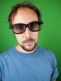 Thirty year old man with 3d glasses is watching a boring movie. Over a green background Stock Photography