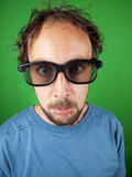 Thirty year old man with 3d glasses watching a sad movie. Over a green background royalty free stock image