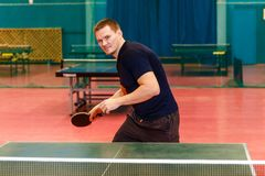 Thirty-year-old man holding a racket for table tennis. Indoors royalty free stock photo