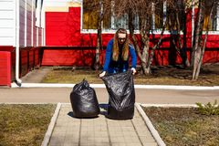 Thirty-year-old woman collects garbage in large plastic bags . Care of the environment, cleaning of the territory, waste disposal. Thirty-year-old woman collects stock image