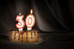 Thirty years anniversary. Birthday chocolate cake with white burning candles in the form of number Thirty. Dark background with black cloth stock photography