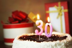 Thirty years birthday. Cake with burning candles and gifts Stock Photography