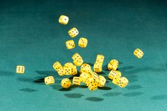 Thirty yellow dices falling on a green table stock image