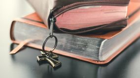 Two bibles are stacked on a black shiny table top. Tho brown leather covered bibles are stacked on top of a black shiny and reflective table top. The bible on stock images