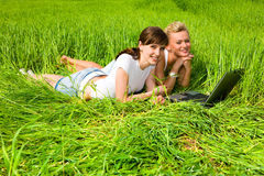 Tho girls laughing near laptop computer outdoors. Two beautiful girls in white clothes are laughing near laptop computer outdoors. Lay on the green grass Royalty Free Stock Photos