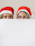 Tho happy girl in santa hat hiding behind a empty blank banner w Stock Image