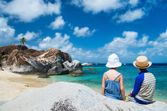 Tho kids enjoying tropical scenery. Back view of two kids sitting on granite boulder and enjoying beautiful scenery of The Baths beach area major tourist Stock Images