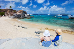 Tho kids enjoying tropical scenery. Back view of two kids sitting on granite boulder and enjoying beautiful scenery of The Baths beach area major tourist Royalty Free Stock Photography