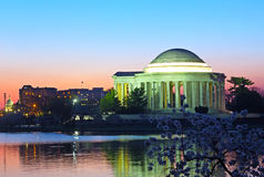 Thomas Jefferson Memorial and Capitol Building at predawn during cherry blossom festival. Landmark reflection in Tidal Basin waters with cherry blooms Royalty Free Stock Photography