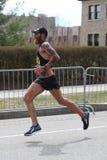 Thomas Puzey de hampe de drapeaux Arizona emballe dans le marathon de Boston venant dans le 16ème avec du moment du 2h18 : 20 le  Images stock