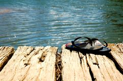 Thongs. A pair of thongs (flip flops) sit on a jetty near the seaside Stock Photography