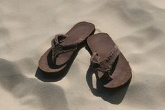 Thongs On Beach. Pair of brown thongs / sandals in sand on beach Royalty Free Stock Photography