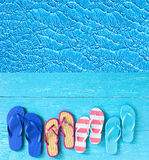 Thongs on the blue planks against blue water Royalty Free Stock Image