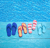 Thongs on the blue planks against blue water Stock Photo