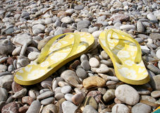 Yellow thongs on the beach. Yellow thongs on the smooth stones detail Royalty Free Stock Image