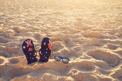 Thongs and sunglasses on beach sand Royalty Free Stock Photo